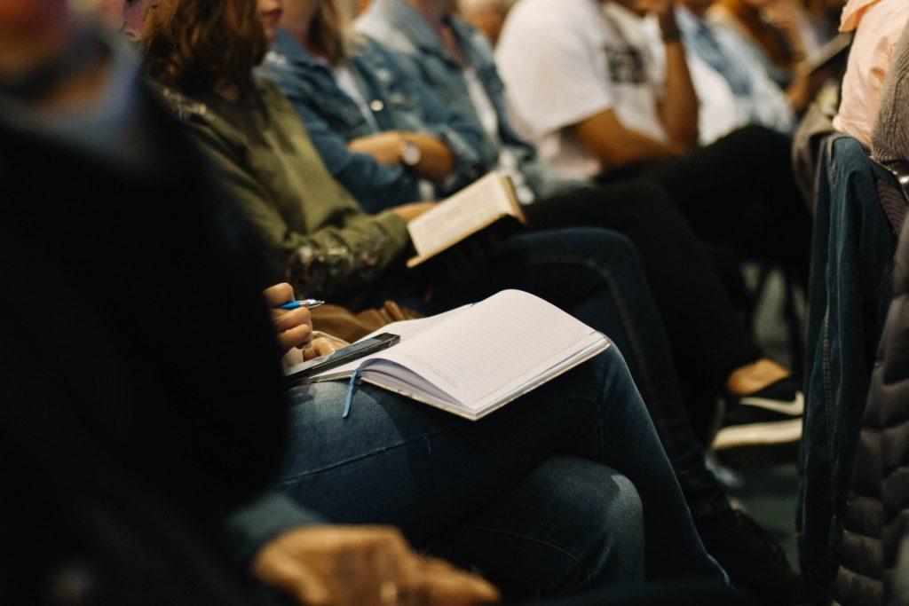 Menschen sitzen nebeneinander. Sie halten Gebetbücher auf dem Schoß oder in der Hand. Ihre Gesichter sieht man nicht.