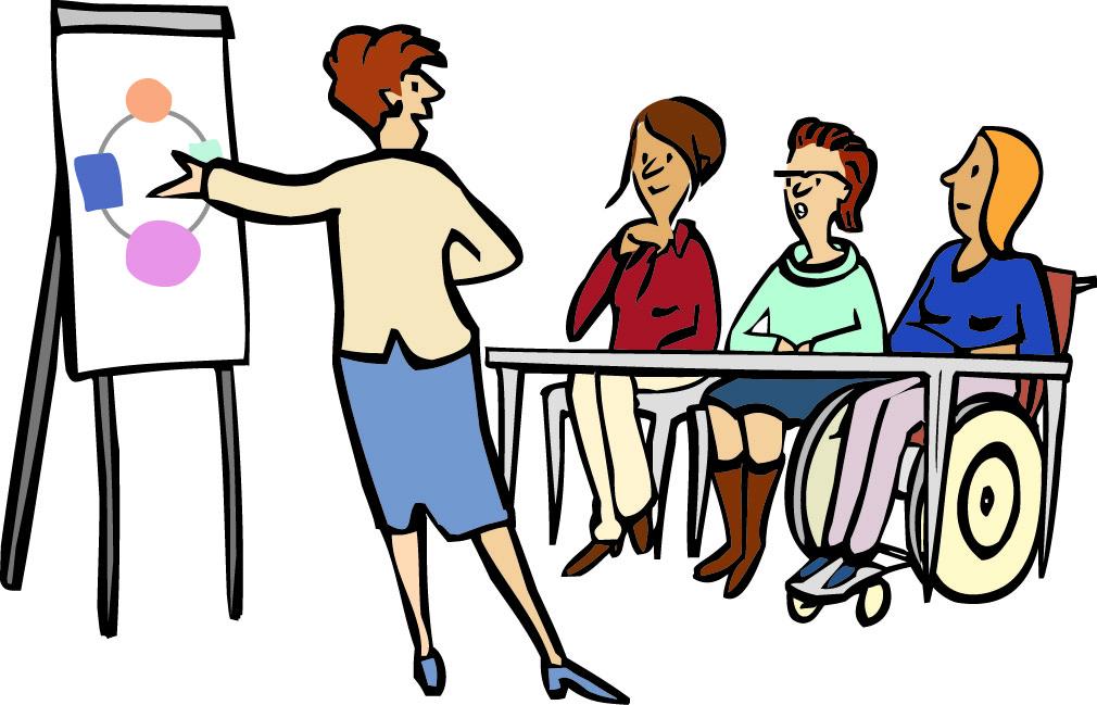 Drei Frauen sitzen an einem Tisch. eine Frau steht vor einer Flipchart und zeigt darauf. Sie erklärt etwas.