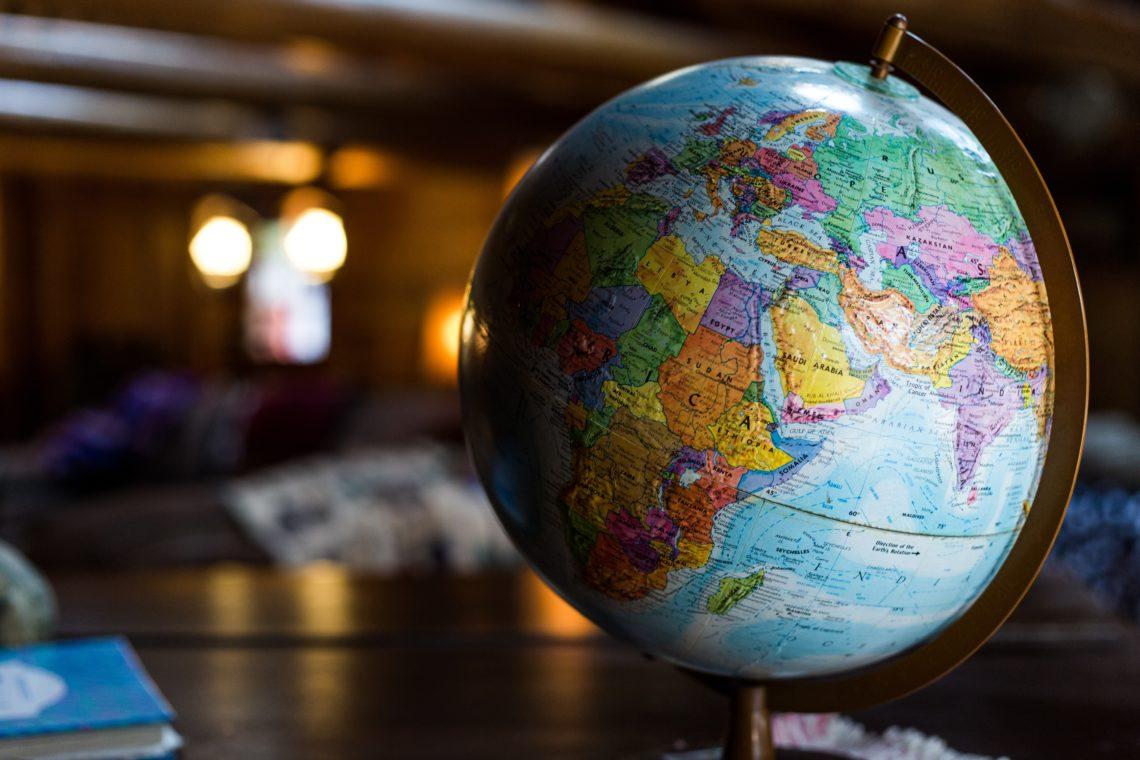 Globus auf einem Tisch in einer dunklen Halle. Deckenleuchter sind im Hintergrund unscharf zu sehen. Die Tischplatte ist blank poliert.