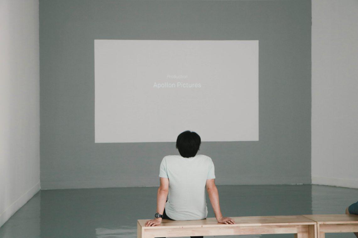 """Mann auf Bank in einem fast kahlen Raum sieht auf eine große fast leere Projektionsfläche. Dort steht """"Apollon Pictures""""."""