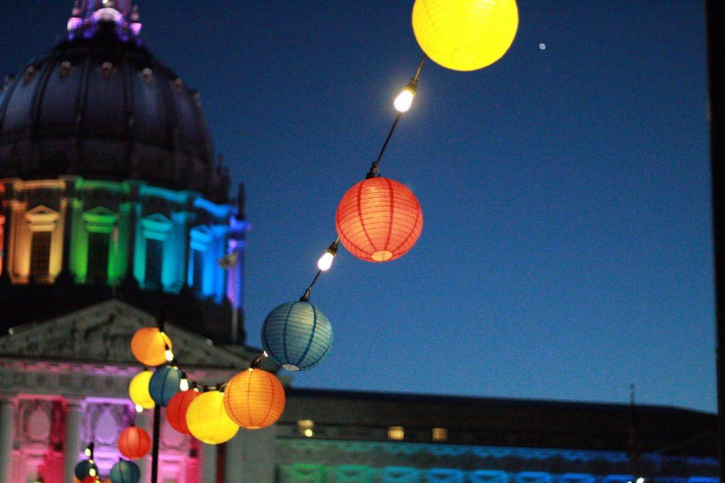 Großes Kirchengebäude bei Nacht, davor eine Kette mit bunten Lampions