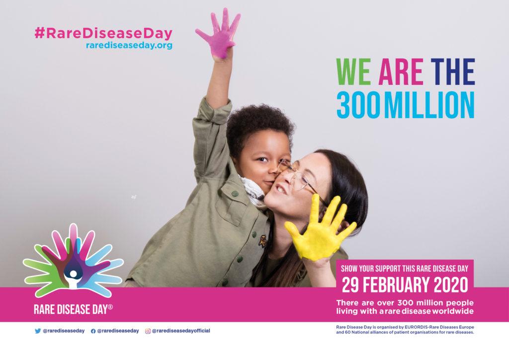 """Ein Junge reckt eine Hand in die Höhe, die bemalt ist. Er schmiegt sich an eine Frau, die selber eine Hand in Richtung Betrachtenden Ausstreckt. Auch Ihre Hand ist bemalt. Veranstaltungsposter des """"rare disease day"""" 2020. Motto: Wir sind 300 Millionen."""