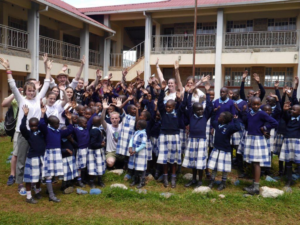 Im Innenhof des zweistöckigen Schulgebäudes stehen Gäste und Schulkinder in Uniformen und recken ihre Hände freudig in die Höhe.