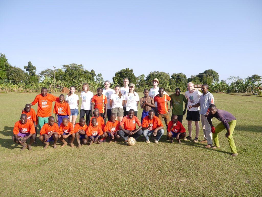 Weite Rasenfläche im Sonnenschein. Am Rand Büsche und Bäume. In der Mitte eine Gruppe aus Jugendlichen in Sportkleidung, die offenbar zwei Mannschaften angehören.
