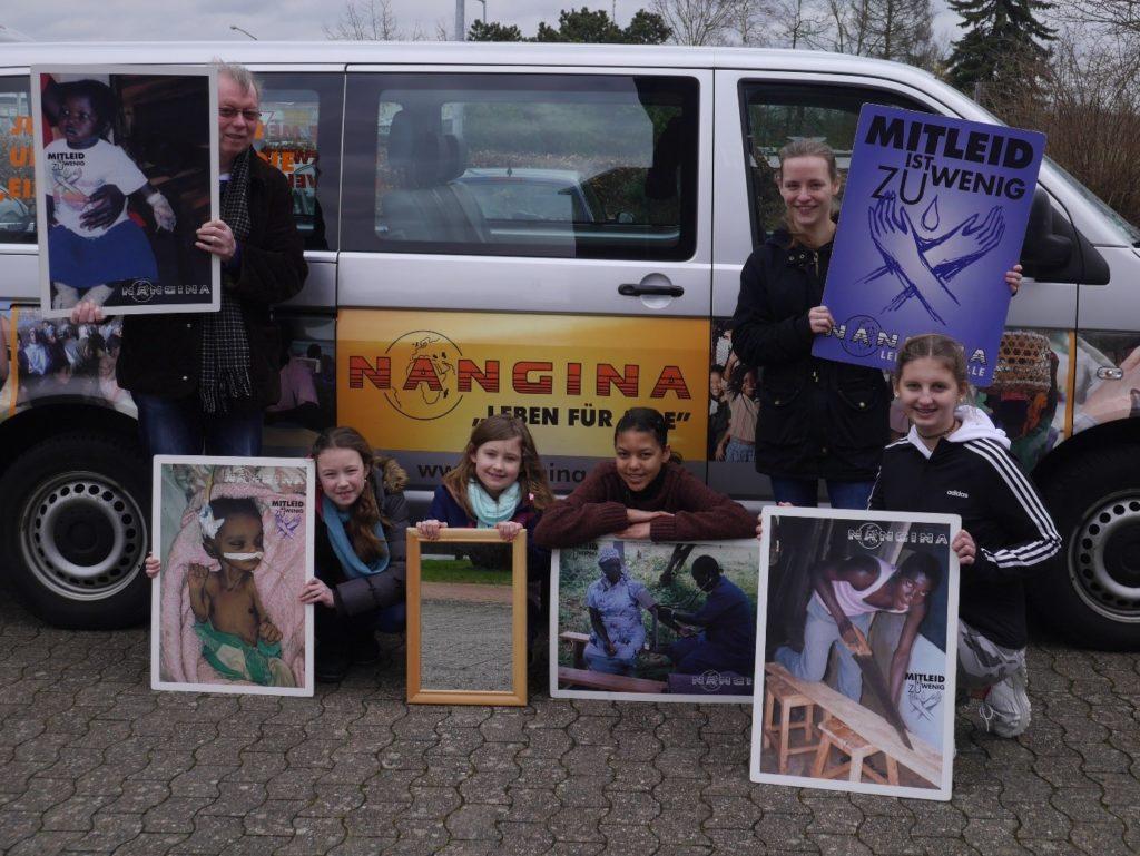 """Kinder und ein Erwachsener halten Plakate mit Bildern ihrer Arbeit hoch. Es sind Menschen in Kenia zu sehen. Ein Mädchen hält das Vereinsplakat mit den gekreuzten Händen und der Aufschrift """"Mitleid ist zu wenig"""". Ein Kind hält einen Spiegel, in dem die Pflasterung des Platzes und der Rasen zu sehen sind. Sie setehn vor ihrem Vereinsbulli. Die Aufschrift NANGINA ist zu sehen."""