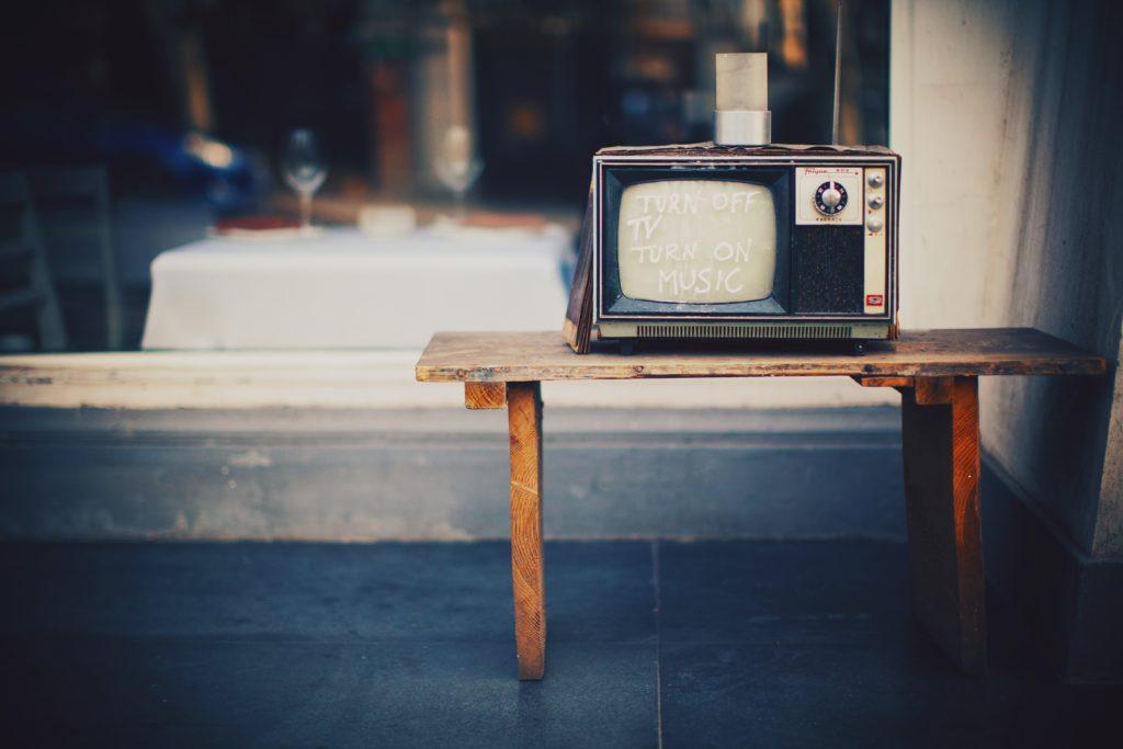 Fernseher auf einem Holztisch, im Hintergrund ein Tisch mit weißer Decke und Weingläsern.