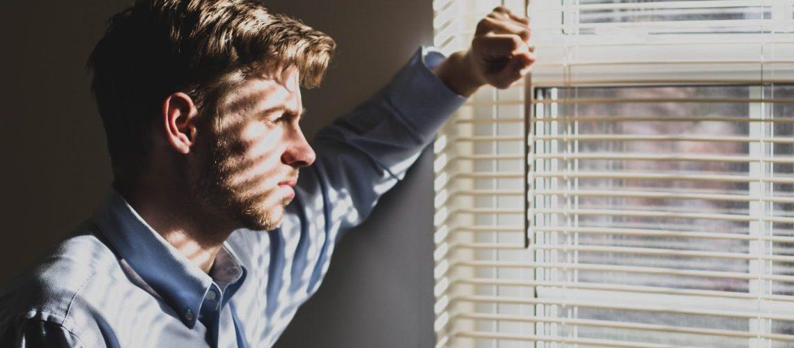 Ein Mann steht innen vor einem Fenster mit Jalousie. Die Jalousie wirft einen Schatten auf ihn. Er schaut traurig ins Leere. Mit dem linken Arm stützt er sich an der Wand ab.