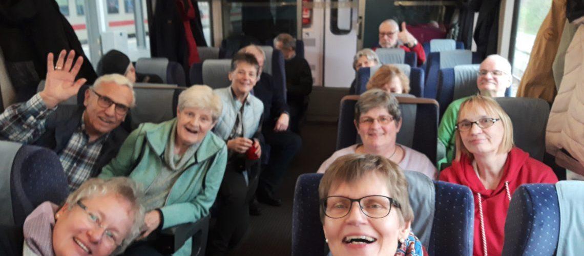 Die Gruppe sitzt in einem Großraumwagen des Intercity. Alle lachen fröhlich in die Kamera.